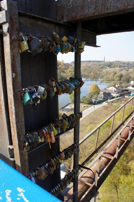 Замочки влюблённых висят на опорной колонне пешеходного моста