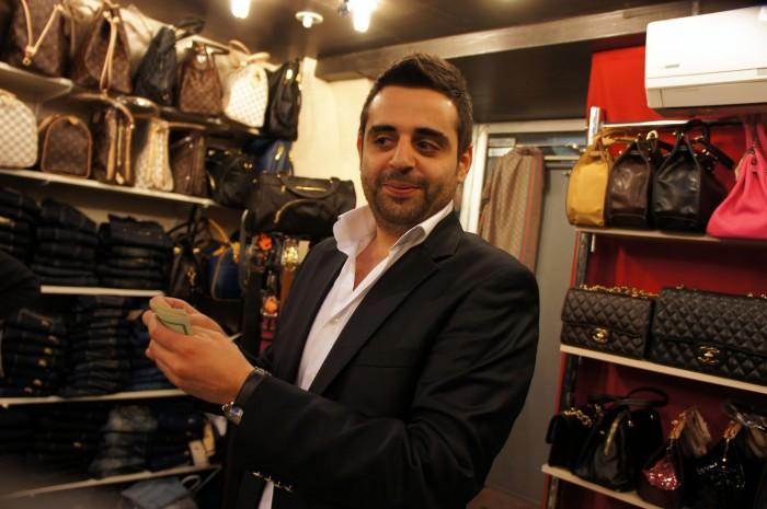 Продавец держит мои доллары в руках. Я уже выбрал новые джинсы себе, они мне понравились, и вот я отдал деньги продавцу...